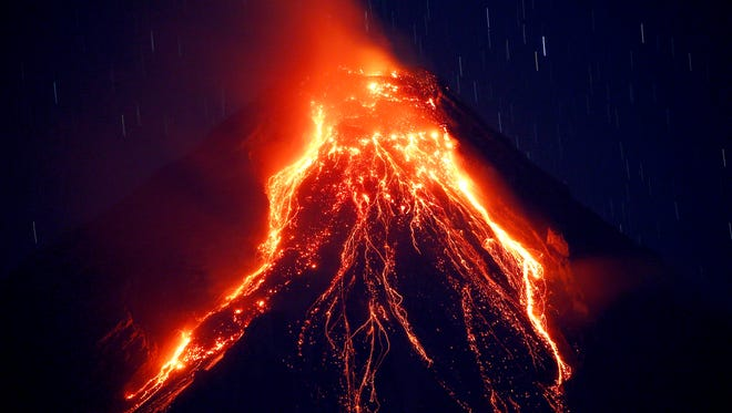 Lava cascades down the slopes of Mayon volcano during its eruption for the second straight day Tuesday, Jan. 23, 2018 as seen from Legazpi city, Albay province, southeast of Manila, Philippines. The Philippines' most active volcano ejected a huge column of lava fragments, ash and smoke in another thunderous explosion at dawn Tuesday, sending thousands of villagers back to evacuation centers and prompting a warning that a violent eruption may be imminent.