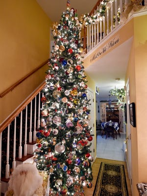 """The Foyer Ball Tree, as seen Monday, Nov. 21, 2016, in Mark and Debbie DeBowes' York Township home. The DeBowes annually set up 20 or more Christmas trees in their York Township house; this year, they put up 24 trees, each themed by color or ornament type. """"It's just rewarding, when it's done, to sit back and look at it and say, 'You know, that is pretty marvelous,'"""" Debbie DeBowes said of the month-long process of setting up the trees by Thanksgiving. """"It really is passion."""""""