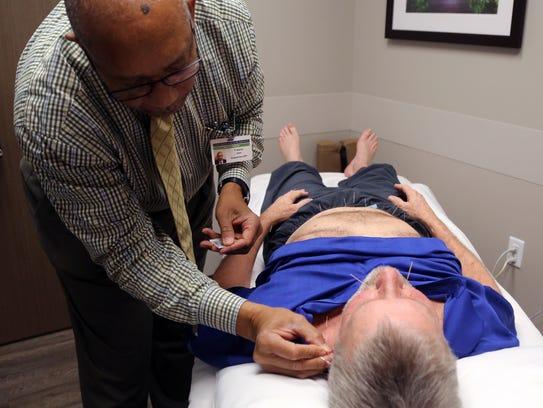 William Harper receives acupuncture treatment from