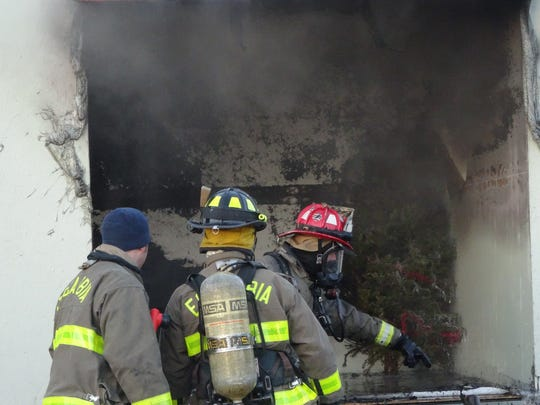 Firemen assess damage caused by a tree catching fire