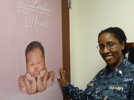 Lt. Cmdr. Edith Glanton, a Naval Hospital certified nurse midwife, stands in front of a poster of a baby she delivered.