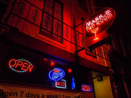 The Mark III Tap Room's signs are lit up outside its previous location on Main Street in this photo from 2015, shortly before the bar closed and moved to South Walnut Street.