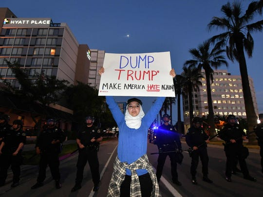Aya Hilali holds up a sign during a protest near where republican presidential candidate Donald Trump held a rally in in San Jose, California on June 02, 2016. Protesters attacked trump supporters as they left the rally, burned an american flag, trump paraphernalia and scuffled with police and each other.