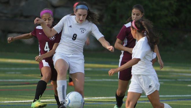 Mamaroneck junior Olivia Rodrigues (9) controls the ball while being defended by Ossining freshman Jaida Strippoli (4) during a game at Mamaroneck High School on Thursday, September 17, 2015. Mamaroneck won 3-0.