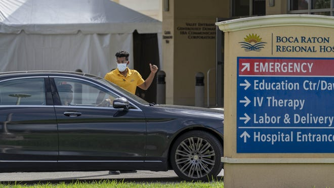 A valet directs people where to park at Boca Raton Regional Hospital Wednesday. The hospital erected the tent in the background to screen patients before entry into the emergency room. Valets were not parking cars to avoid potential contact with the coronavirus.