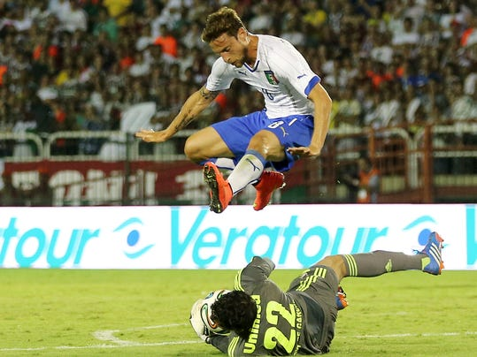 Italy's national soccer team player Claudio Marchisio, top, jumps over Fluminense goalkeeper Diego Cavalieri during a World Cup warm up soccer match between Italy and Fluminense at the Cidadania stadium, in Volta Redonda, Brazil, Sunday, June 8, 2014. Italy plays in group D of the 2014 soccer World Cup. (AP Photo/Antonio Calanni)