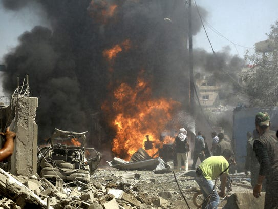 Residents gather at the site of a bomb attack in Syria's