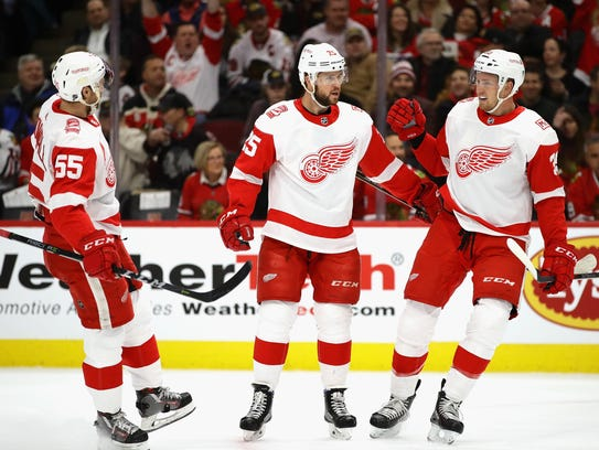 Red Wings' Mike Green, center, is greeted by Niklas