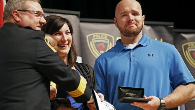 Retired Springfield Police officer Aaron Pearson receives a Purple Heart from Springfield Police Chief Paul Williams.