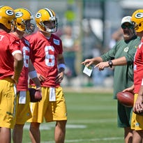 From left, Green Bay Packers quarterbacks Brett Hundley (7), Scott Tolzien (16), Matt Blanchard (6) and Aaron Rodgers (12) talk with coach Alex Van Pelt during minicamp at Clarke Hinkle Field in June.
