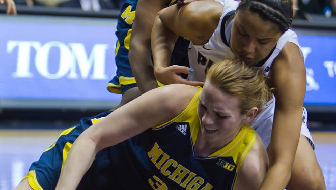 Purdue's Liza Clemons, 23, fights Michigan's Val Driscoll, 34, for a loose ball Wednesday, January 15, 2014, at Mackey Arena in West Lafayette. Purdue lost 65-49.
