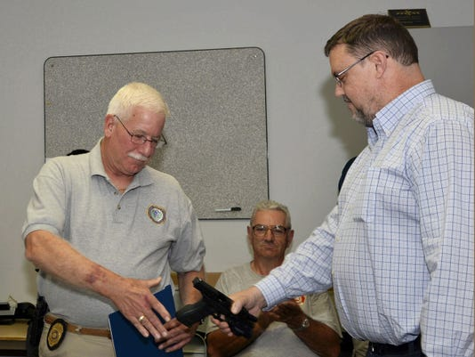 "Cleona Borough Police Chief Raymond J. Barry III accepts his service revolver, that was retired and presented as a gift from the Borough in appreciation for his years of service to the community,  from Council President William ""Jim"" O'Connor. Chief Barry will retire after more than 20 years of service on August 21. Also on hand for the presentation on Monday evening were Officers Matthew Raiger and Robert Henning."