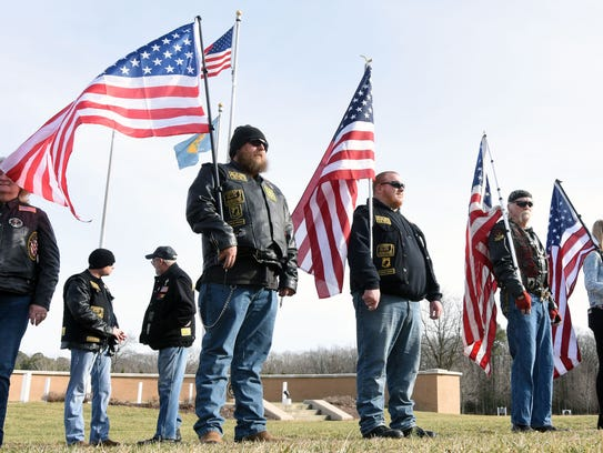 Veterans stand in honor during funeral service for