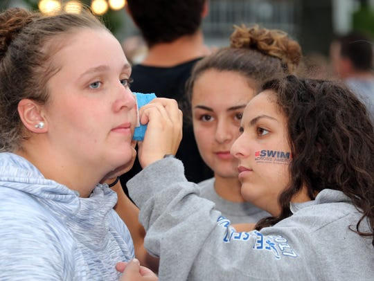 Frankie Garces, right, applies a tattoo to the face