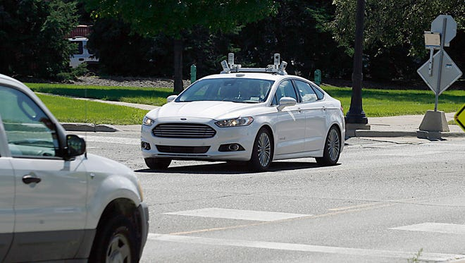 A Ford Fusion Hybrid autonomous test vehicle navigates a 4-way intersection at the Ford Product Development Center facilities in Dearborn in Sept. 2016.