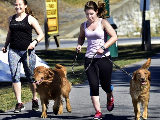 Inna Caruso, left, and Jordan Massey jogged along the Chambersburg Rail Trail with dogs Mac and Nessie on a warm March 9, 2016.