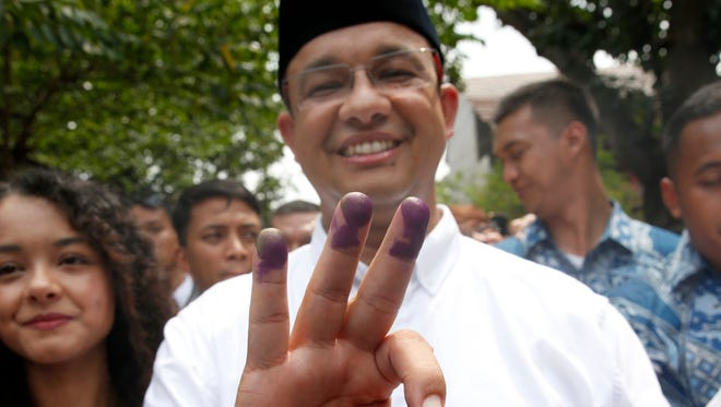 Anies Baswedan displays his ink marked fingers after voting at a polling station in Jakarta, Indonesia, on April 19, 2017.