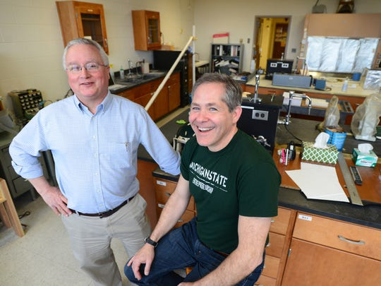 MSU chemistry professors Gary Blanchard, left, and Marcos Dantus pose for a portrait at a lab in the Chemistry Building at Michigan State University on Thursday, March 10, 2016. The two have created a product, which fits in an athletic headband, to test high impact collisions. Depending on the G-force absorbed on impact, the strip will display circles then stars. While the device does not show whether an athlete has a concussion, it can help trainers know when a player needs further examination.