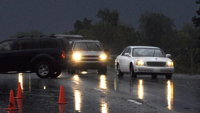 Traffic is shown on Old 27 in St. Johns during a storm in 2008. The writer comments on traffic enforcement along the road in Clinton County.