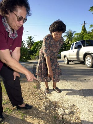In this 2001 file photo, Tamuning/Tumon Mayor Connie Duenas, right, and Vice Mayor Nancy Leon Guerrero show the holes along San Vitores Road, in Tumon.