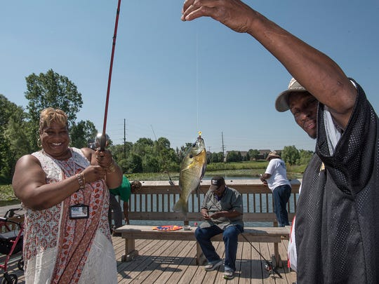 Regina Thompson catches a bluegill. Edmoun Spears helps