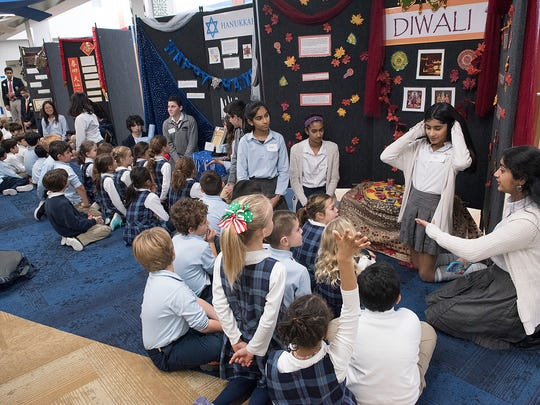 High school students at Detroit Country Day explain holiday celebrations from different cultures to second graders.