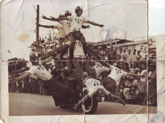 Armando Ramirez, father of Cuban harlista Antonio Ramirez, seen second from left, performs with other members of a Cuban police officer acrobatic squad on Harley-Davidson motorcycles during a carnival celebration in a town outside of Havana in March 1964. (Photo courtesy of Antonio Ramirez.)