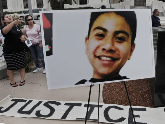 A photo of Jonathan Hernandez is displayed at a 2016 news conference in front of Ventura City Hall that announces the filing of a lawsuit against tow-truck driver Martin Henderson, the city of Ventura and Ventura County.