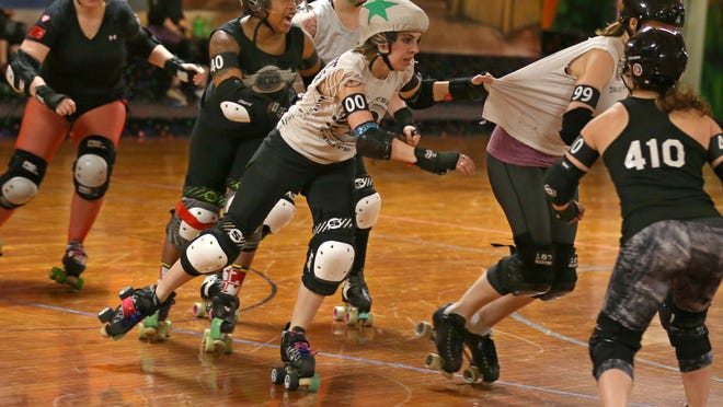 """Renee """"Synthetic Delusion"""" Ast of Henrietta, center, uses a Rotties teammate to help lead the way as she works her way through a pack of Haters during the Roc City Roller Derby league practice March 12 in Greece."""