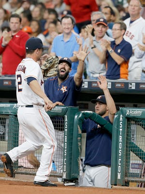 Houston Astros third baseman Alex Bregman (2) gets high fives from the dugout after making a play at third base against the New York Yankees in the first inning at Minute Maid Park.