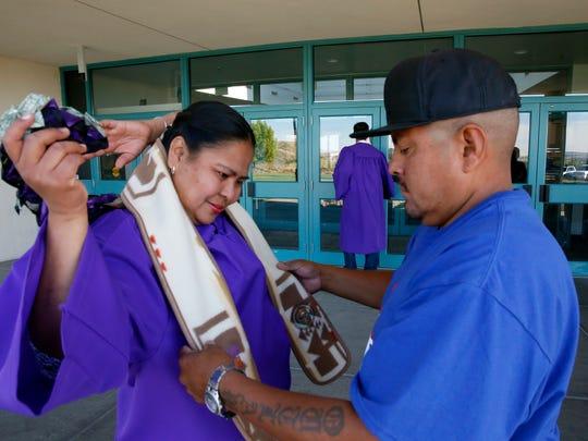 Regina Yazzie, left, gets help preparing for the San Juan College commencement ceremony from her boyfriend Matthew Genecha outside the Henderson Fine Arts Center on Saturday.