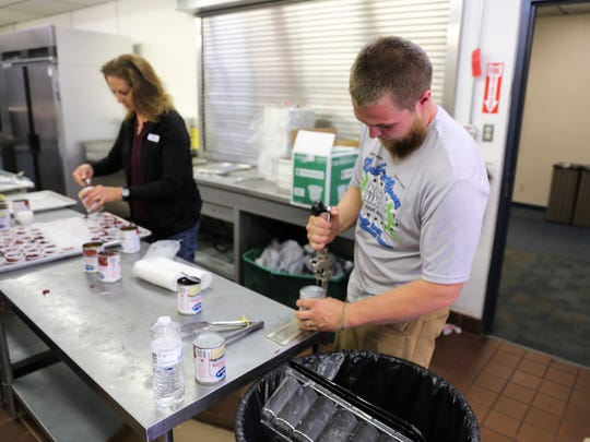 Sheri Korte, left, dishes out cranberry sauce while Wesley Therrien opens cans as part of the Salvation Army Thanksgiving meal on Thursday at the Farmington Civic Center.