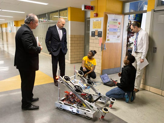 From top left, Henry Ford High School Principal Michael Mokdad, Detroit School District Superintendent Nikolai Vitti and Henry Ford High School english teacher and robotics coach, Gary Mobley, while students Zaakya Artis, 16, bottom left, and Calvin Harvey, 14, work on a robot on Wednesday, May 9, 2018 at Henry Ford High School in Detroit. Detroit School District Superintendent Nikolai Vitti has spent one year in this position.