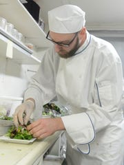 Ryan Rathburn prepares a Greek Salad for a diner at the Blue Collar Bistro's new location at 921 E. State St. in Fremont on Thursday.