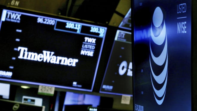 In this June 13, 2018, file photo, the logos for Time Warner and AT&T appear above alternate trading posts on the floor of the New York Stock Exchange.