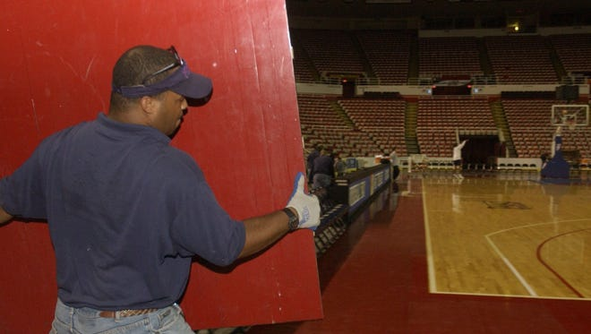 Greg Blair from Holland  prepares to put a floor panel in place for the basketball court on Sept. 23, 2004, before the Detroit Shock practice at Joe Louis Arena.
