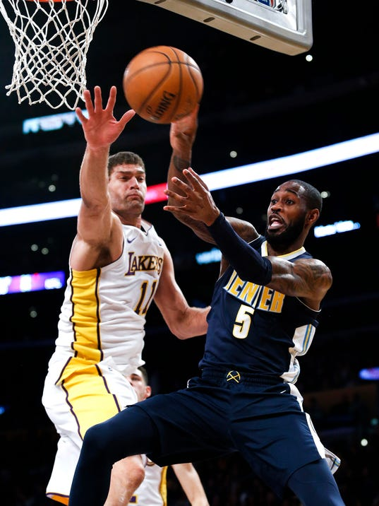 Denver Nuggets guard Will Barton, right, looks to pass the ball against Los Angeles Lakers center Brook Lopez during the first half of an NBA basketball game Sunday, Nov. 19, 2017, in Los Angeles. (AP Photo/Ringo H.W. Chiu)