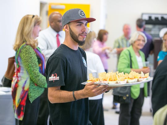 Employee David Lee serves hors d'oeuvres at the new