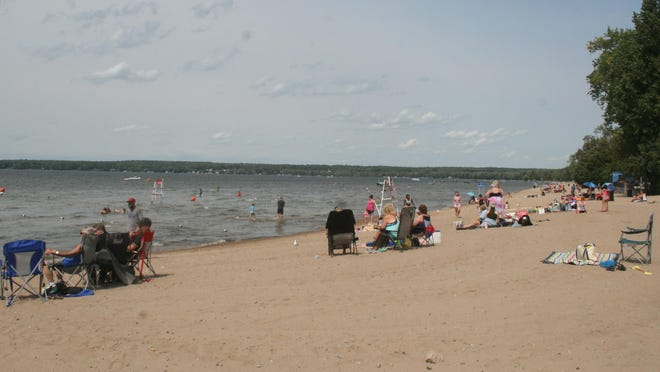 Visitors sit at the edge of Oneida Lake in Sylvan Beach on Sept. 7, 2020.