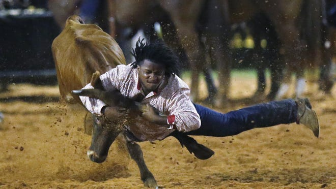 Dorian Autman competes in the Bull Doggin' event at the 65th annual Okmulgee Roy LeBlanc Invitational Rodeo, the nation's oldest all-black professional rodeo event, in Okmulgee on Saturday.