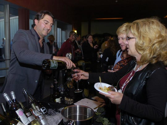 Sonny Mio, with Park Place Fine Wine Spirits, pours a glass for Michele Reading and Lori Laird.