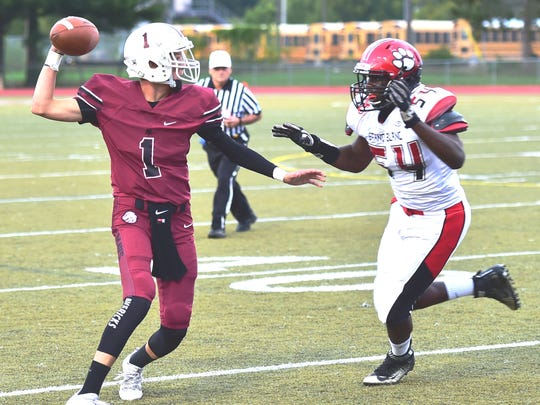 Milford's Aiden Warzecha (left) makes the pass pressured by Grand Blanc's Khalen Parker.