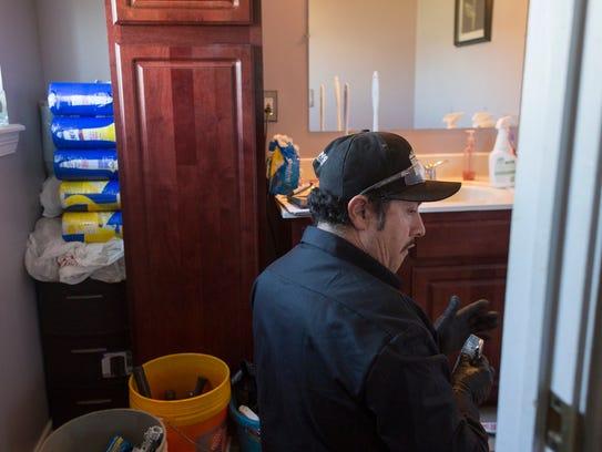 Benkari plumber Raymundo Gonzales, works to remove