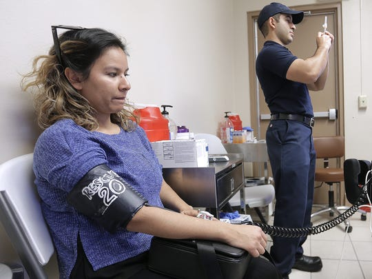 Lucia Aguirre has her blood pressure taken while El Paso firefighter Alejandro Garcia prepares a flu vaccine in January 2017 at the El Paso Fire Department's Safety and Health Outreach Center, 5415 Trowbridge Drive.