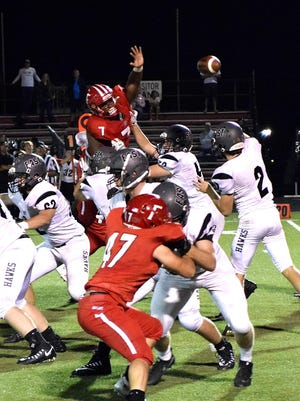 Lakota East quarterback Dylan Fry lifts a pass over the outstretched hands of Fairfield's Malik Vann (7) Sept. 15.