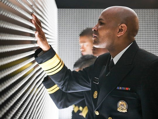 "Surgeon General Jerome Adams touching ""The Pill Wall"" at the National Safety Council's Prescribed to Death Memorial which was on display on the Ellipse in President's Park at the White House before other stops around the U.S. Each pill depicts one of 50 faces of the 22,000 people who died as a result of opioids in 2015."