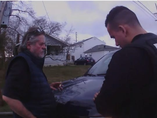Robert T. Merriken Sr., speaks with a police officer