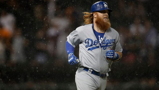 Los Angeles Dodgers 3rd baseman Justin Turner (10) jogs to first base during a rain storm in the game against the Chicago White Sox at Guaranteed Rate Field.