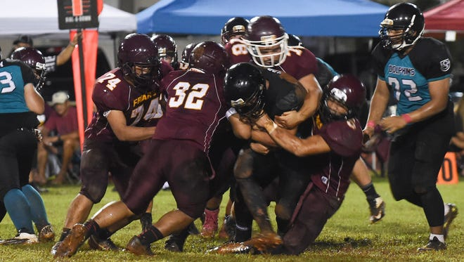 The Father Duenas Friars defense takes down a Southern High Dolphin during their Interscholastic Football League game at George Washington High School field in Mangilao on Sept. 12.
