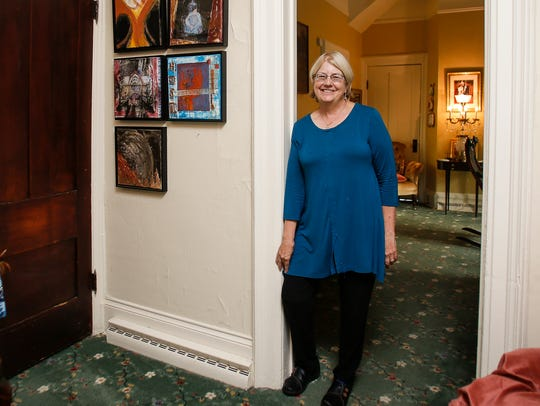 Saralee Howard poses among some of her paintings at